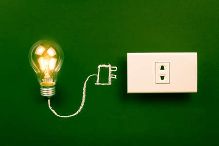 Unplugged light bulb still shining, energy saving creation or business idea concept