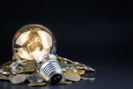 Light bulb and pile of coins, can be used as business idea or energy saving concept photo