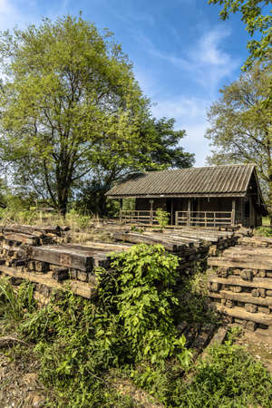 Abandoned house with pile of bolster wood near train station in rural of Thailand photo