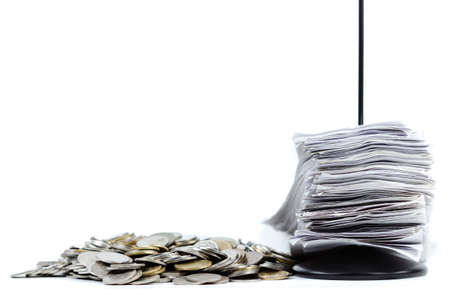 Stack of receipts in paper nail with pile of coins on white background photo