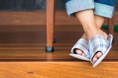 Closeup woman feet in cloth slippers on clean wood floor photo