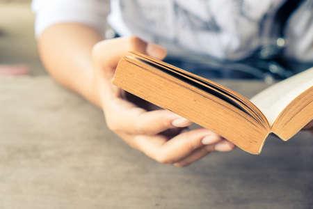 persona leyendo: Mano de la mujer del primer que sostiene el libro de bolsillo para leer Foto de archivo