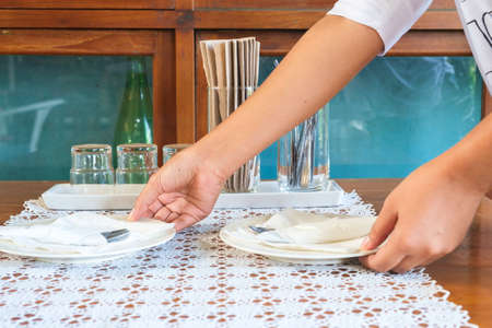 meal preparation: Waiter hand place dishes on the table, meal preparation Stock Photo