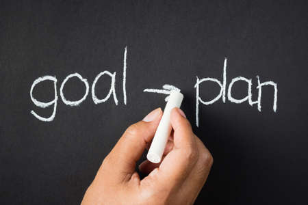 proceed: Hand writing Goal and Plan word proceed with chalk Stock Photo