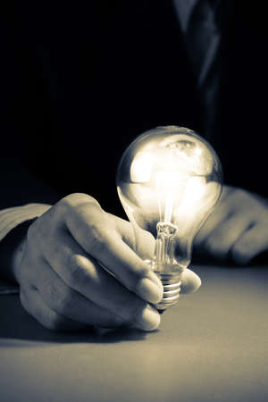 Businessman hold glowing light bulb in the darkness