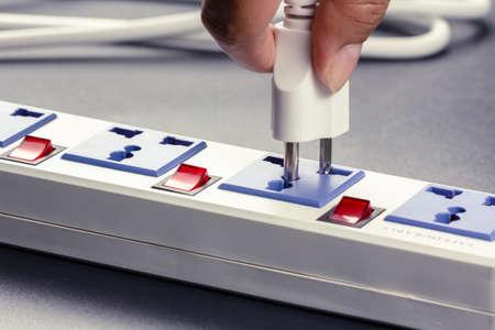 Closeup hand insert plug into multiple socket bar