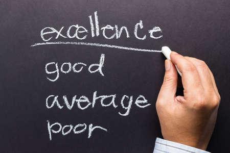 underline: Hand underline Excellence word on audit with chalk