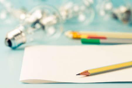 escribiendo: L�piz sobre papel transparente con bombilla como concepto de escritura creativa Foto de archivo