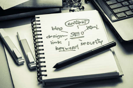 topic: SEO concept and topic, handwritten in notebook with part of laptop, pen, and book on the desk