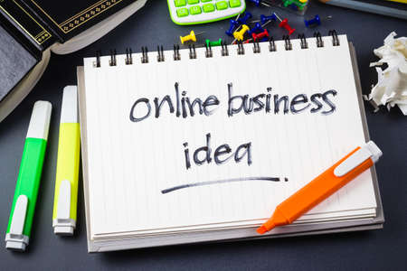 internet business: On the desk with handwriting of Online Business Idea word in notebook Stock Photo