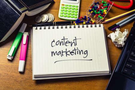 esquema: De escritura a mano de contenido palabra marketing en el cuaderno sobre la mesa de madera