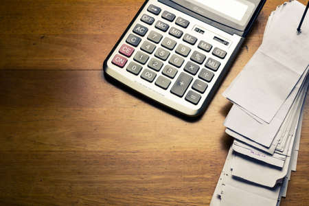 Pile of receipts and calculator on wood table