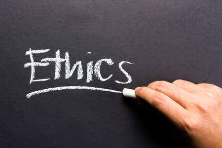 rightful: Hand writing Ethics topic on chalkboard Stock Photo