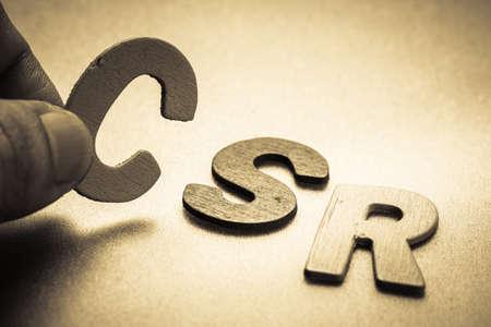 csr: Primer dedo recogiendo una peque�a carta de Ingl�s para poner en la RSE (responsabilidad social corporativa) abreviatura
