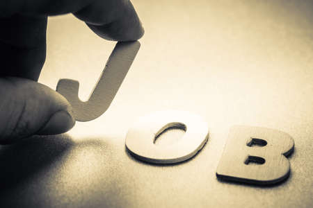 small articles: Closeup finger picking a small English letter to put in the Job word Stock Photo
