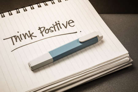Handwriting of Think Positive word as memo note on spiral notebook photo