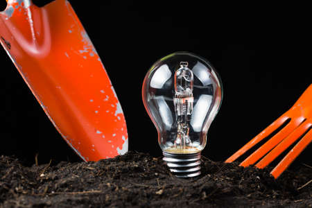 Light bulb as idea symbol in soil with shovel to dig Stock Photo