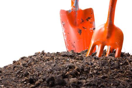Orange shovels dig in soil isolated on white background