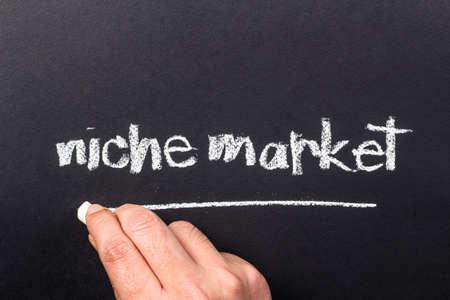 underline: Hand underline Niche Market word on chalkboard