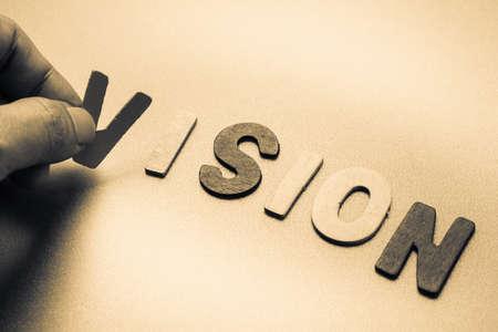 Vinger kies een houten letters van Vision woord