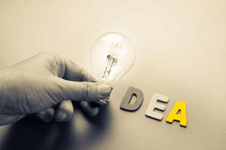 idea: Hand hold light bulb as symbol of Idea word