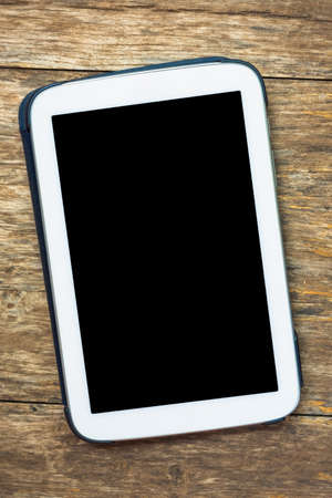 White tablet isolated black screen on wood background photo