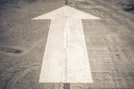 one lane street sign: Arrow straight traffic sign on concrete road Stock Photo