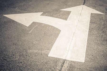 Separate arrow traffic sign on concrete road Standard-Bild