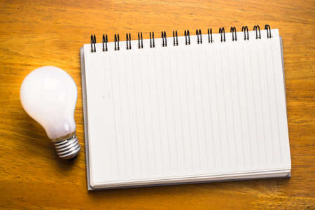 Spiral notebook with light bulb on wood background