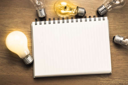 Spiral notebook with light bulbs on wood background 스톡 콘텐츠