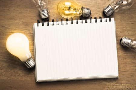 Spiraal notebook met gloeilampen op houten achtergrond Stockfoto