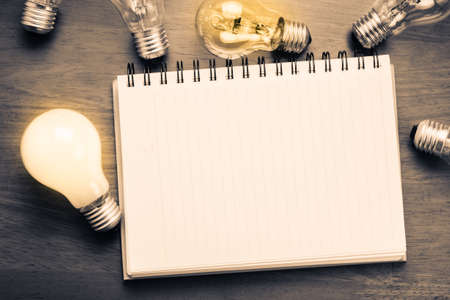 Spiral notebook with light bulbs on wood background Stock Photo