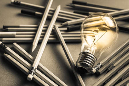 Creative writing, light bulb and many pencils on the table