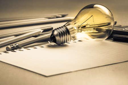 Creatief schrijven, gloeilamp en vele potloden op tafel Stockfoto