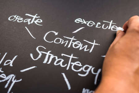 content writing: Hand writing Content Strategy concept on black paper