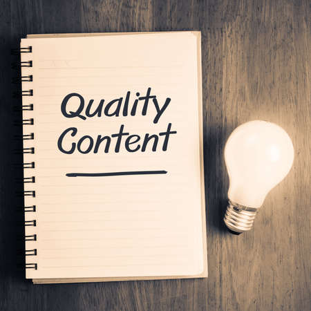 Quality Content topic on notebook with glowing light bulb Stockfoto