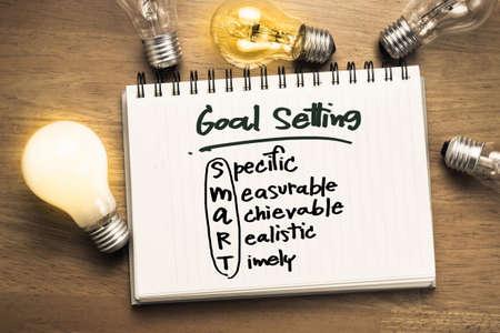 El establecimiento de objetivos como nota en el cuaderno con muchas bombillas