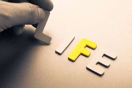 arrange: Hand arrange wood letters as Life word