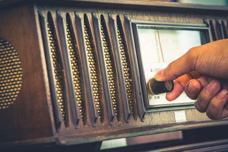 oir: A su vez la mano Primer en la vieja radio para escuchar, estilo retro de color Foto de archivo
