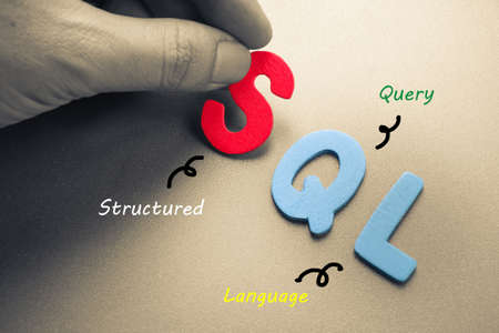database: Hand arrange wood letters as SQL computer language Stock Photo
