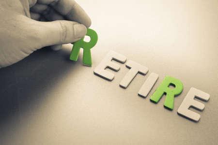 retire: Hand arrange wood letters as Retire word