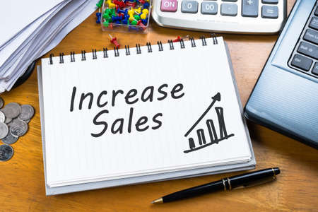 Increase Sales on notebook with part of laptop, receipts and calculator Archivio Fotografico