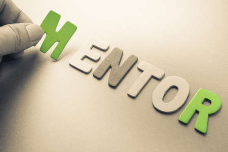 mentoring: Hand arrange wood letters as Mentor word Stock Photo