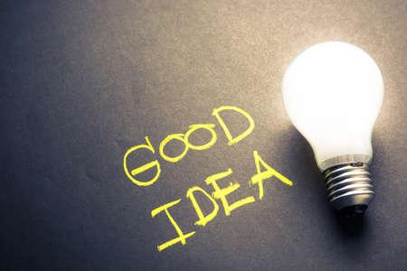 Handwriting of Good Idea on chalkboard with glowing light bulb
