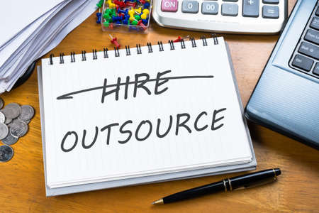 Outsource memo in notebook with part of laptop, receipts and calculator Stock Photo