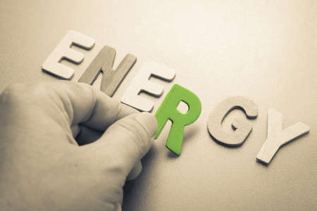 Hand arrange wood letters as Energy word