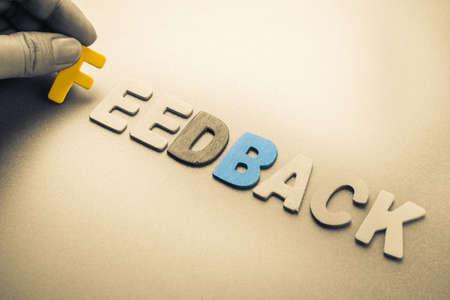 Hand arrange wood letters as Feedback word