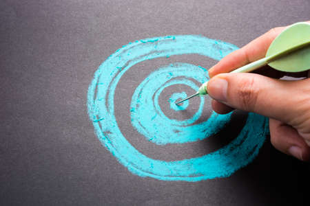 Set goal or accurate planning, hand take a dart into the center of sketching dartboard Stockfoto