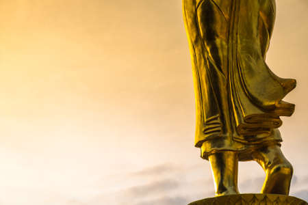 buddha: Abstract Buddha statue, closeup at legs and foot step on morning sky background Stock Photo