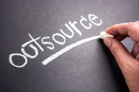 outsource: Hand writing Outsource word topic on chalkboard